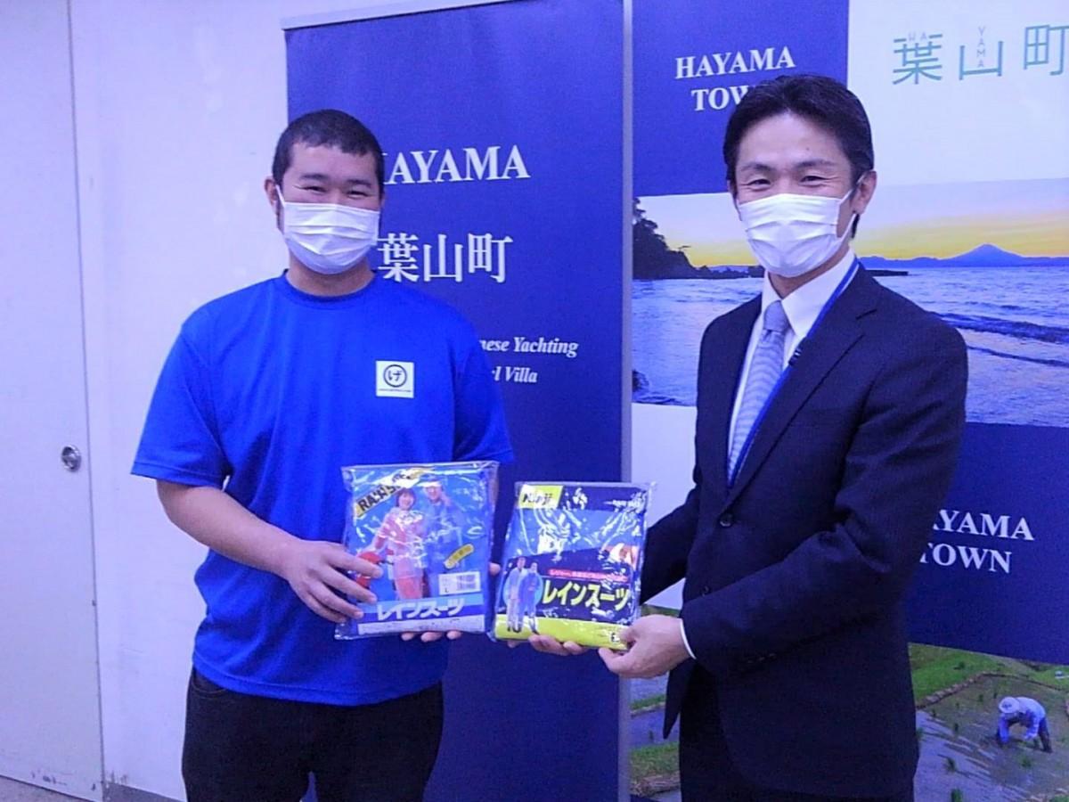 ゲンベイ商店の社長、葉山英三郎さんがレインコート約100枚を山梨崇人町長に寄贈