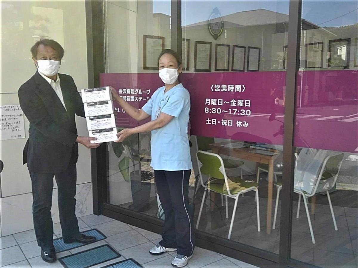 「ずし呑み実行委員会」の山上委員長から寄贈されたマスクを受け取る「けいすい訪問看護ステーション逗子」の大門幸代さん