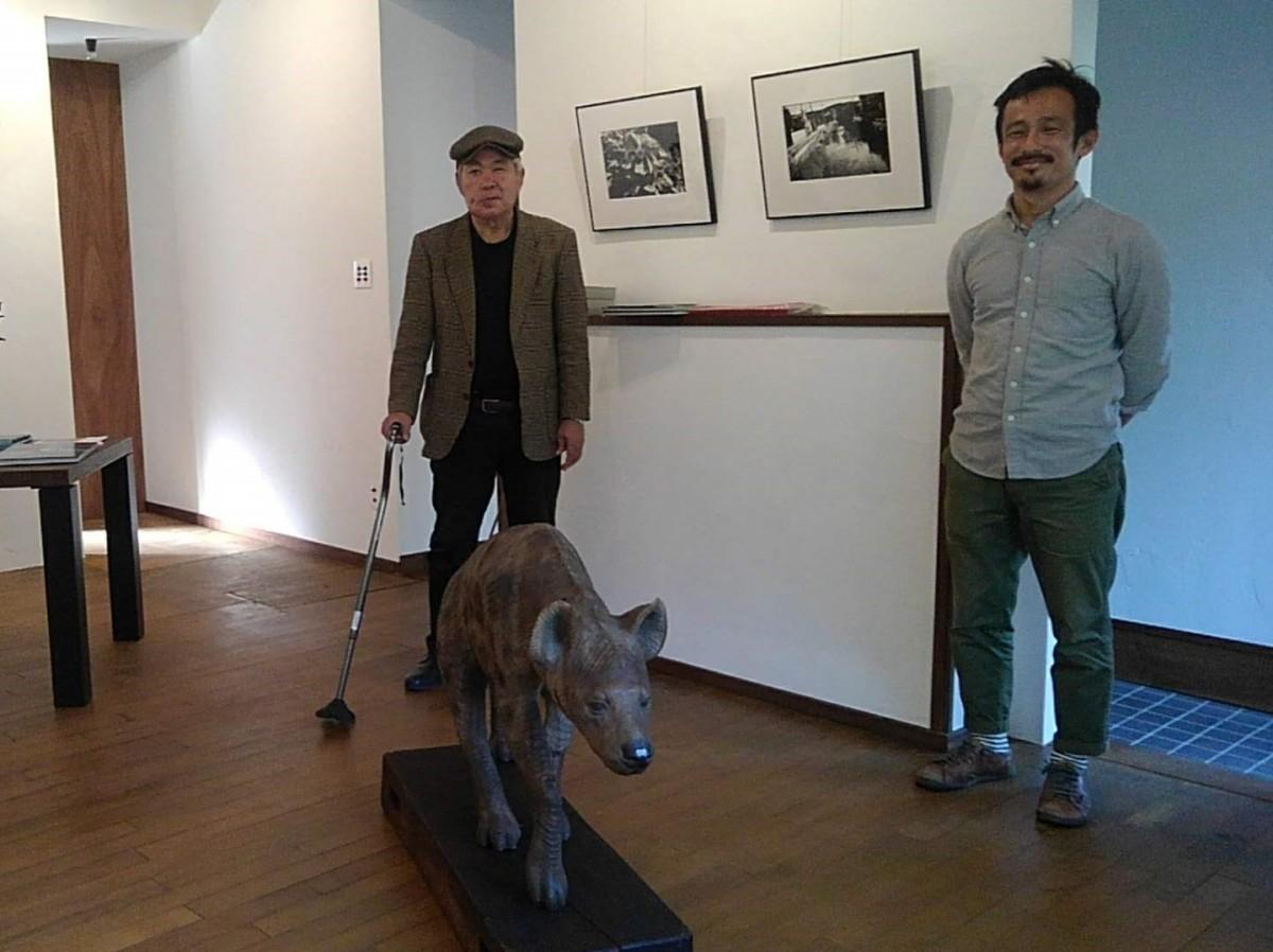 第2展示室に(左から)アーティストの田口弘勝さんと浦部裕光さん。木彫りのハイエナは浦部さん作品