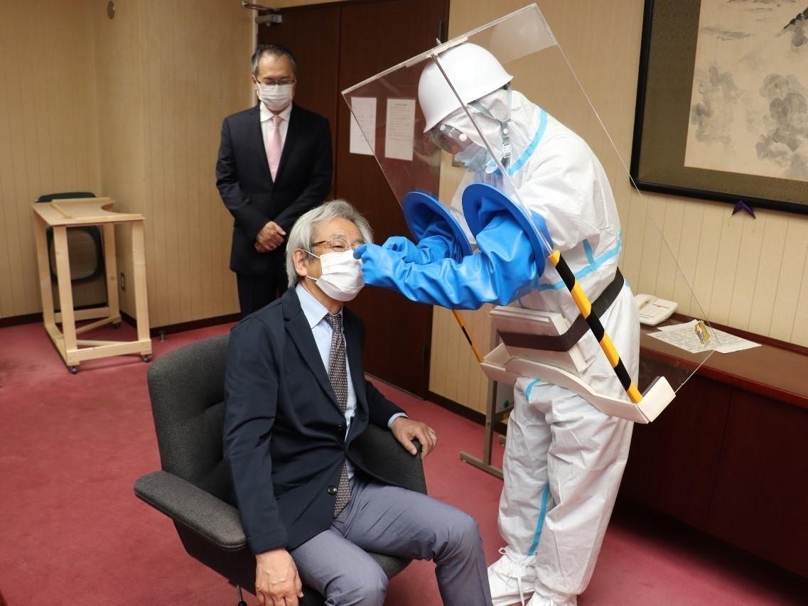 逗子市役所市長室で、PCR検査ボックスを装着して説明(提供=逗子市)