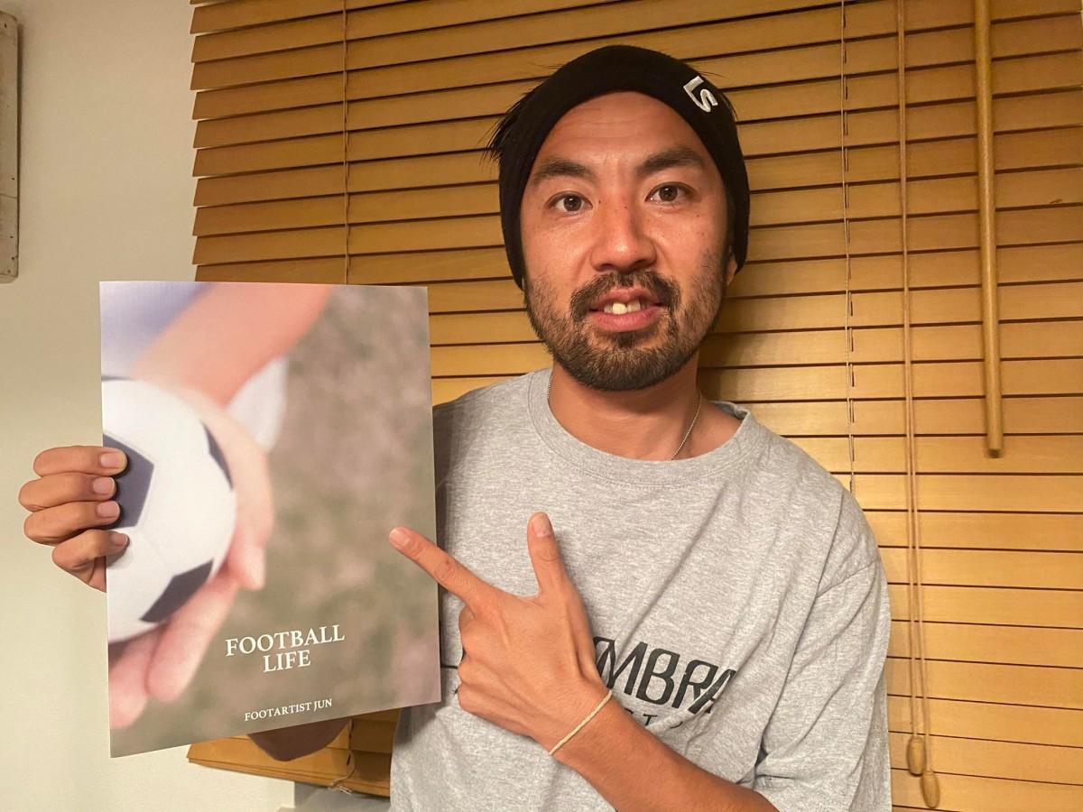 写真集「FOOTBALL LIFE」を手にするアーティストJUNさん(提供=JUNさん)