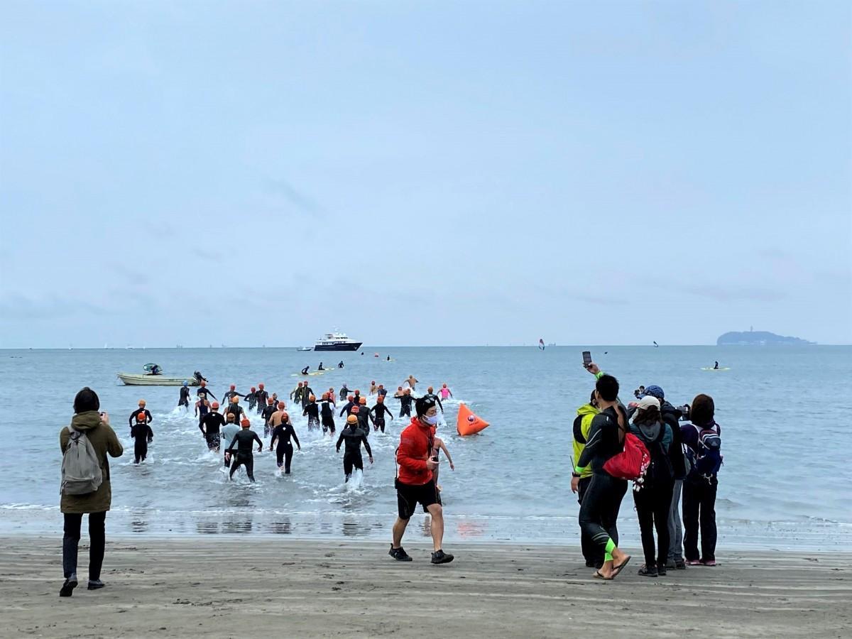 海に入っていくショートの部の参加者。右手には江の島が見える