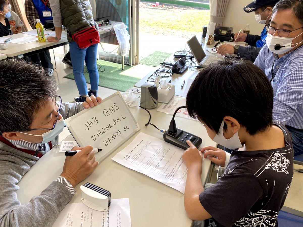 「こちら8J1YACです。QRA(名前)は」と県外の相手と交信体験する小学4年生