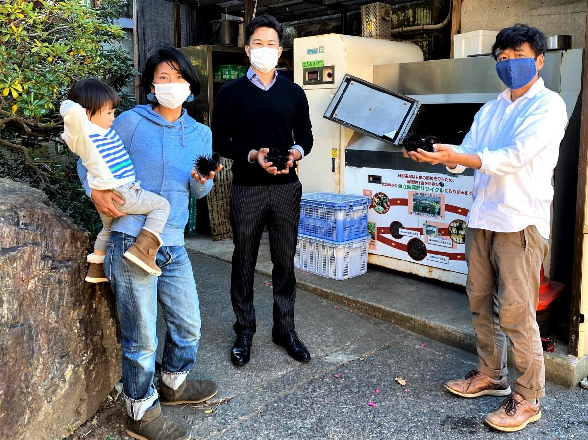 (左から)漁師の畠山晶さんと長男、日影茶屋の社長、角田晋之助さん、葉山アマモ協議会の山木克則さん。ヤサイクルの機械の前で