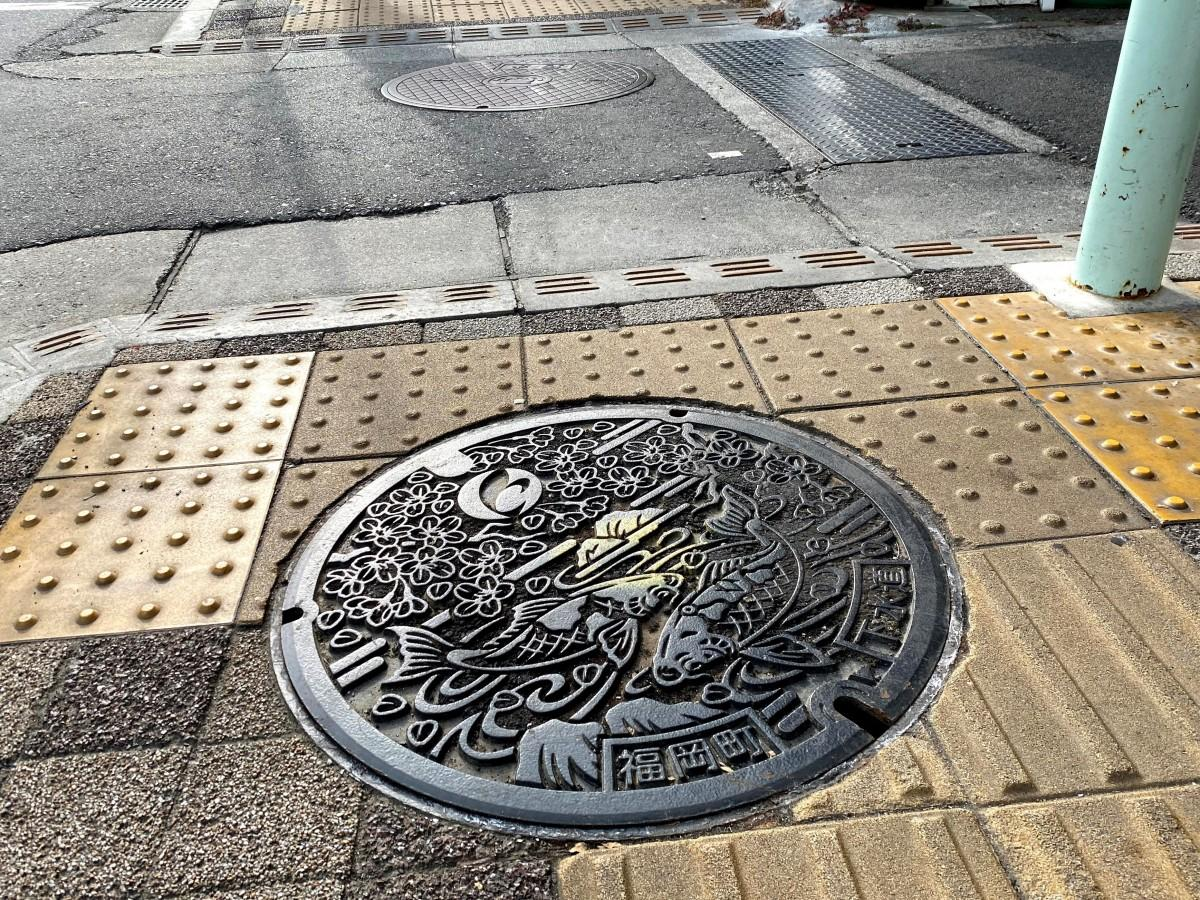 2005(平成15)年に高岡市に合併された旧西礪波郡福岡町のデザインふた。桜と鯉があしらわれている