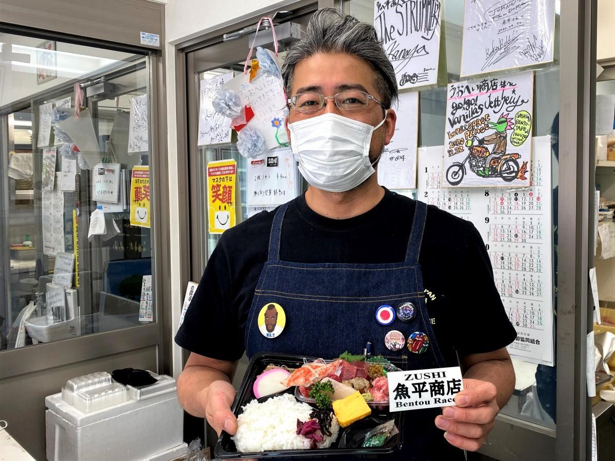 「うおへい」の店主、和田大輔さんの一押し「刺し身弁当」とステッカー。(右上)来店したバンド「Go!go!vanillas」のジェットセイヤさんの色紙も