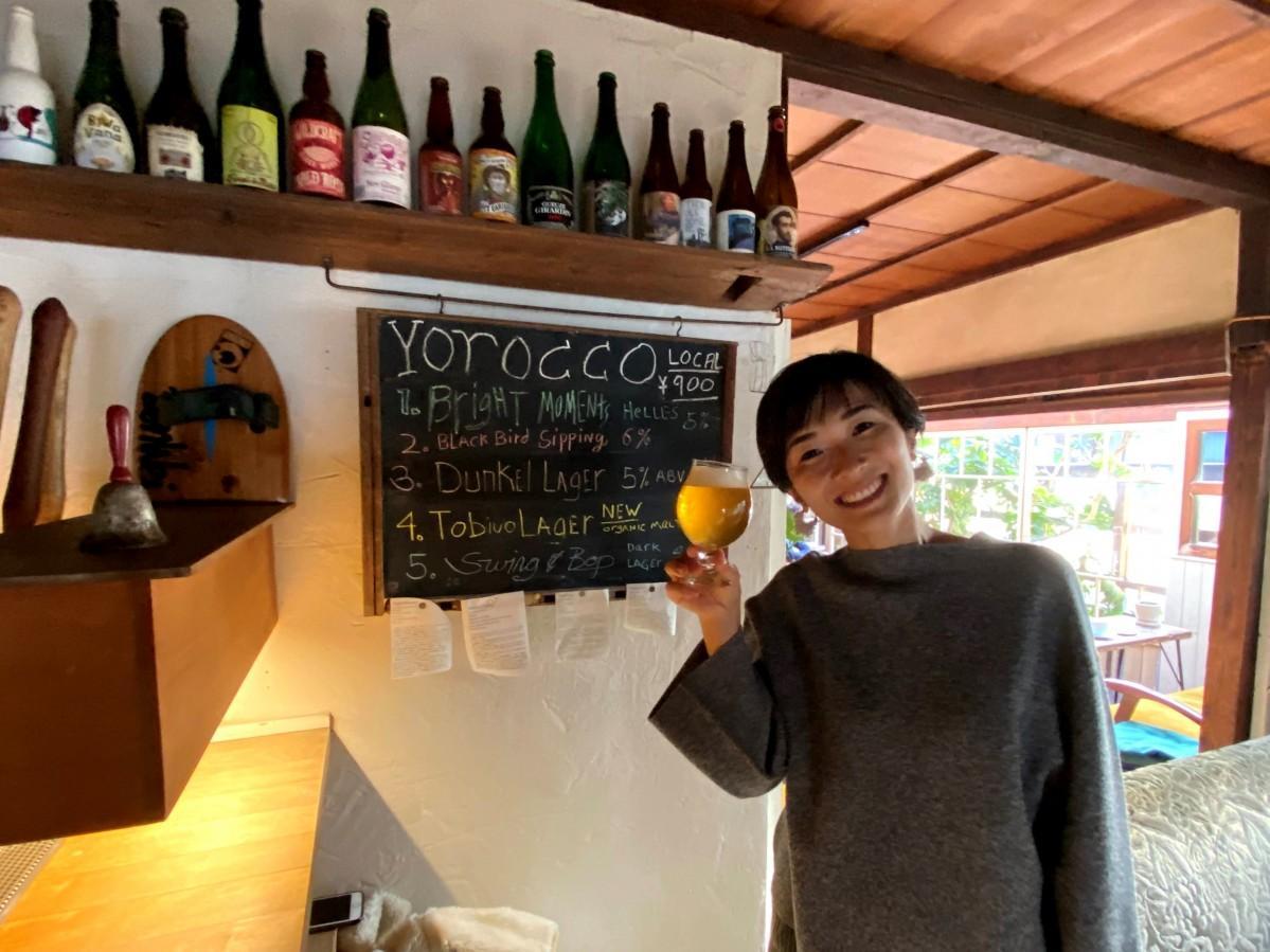 逗子のカフェ「ビーチマフィン」のタップルームで「とびうおラガー」を手にする「とびうおクラブ」のメンバー、小野寺愛さん