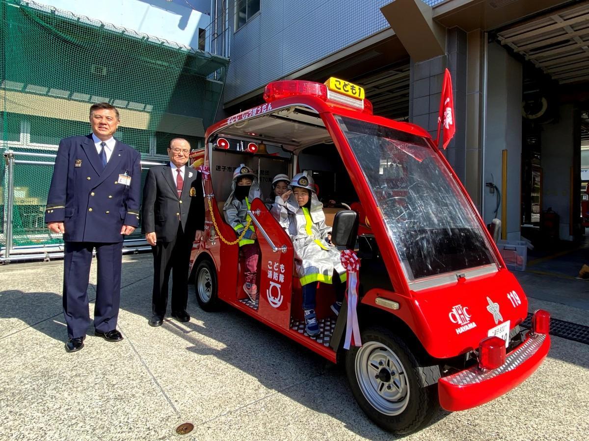 「ミニ消防車完成披露式」で地域の子どもが試乗。(左から)逗子市消防本部の林行雄消防長、葉山国際カンツリー倶楽部の及川善規総支配人