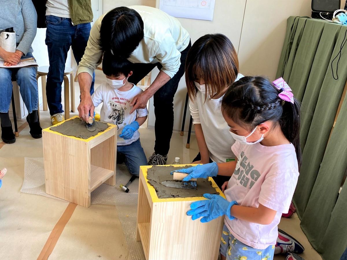 左官職人の高橋直彦さんの指導で、こてを使い、天板に土を平らに塗っていく小学生