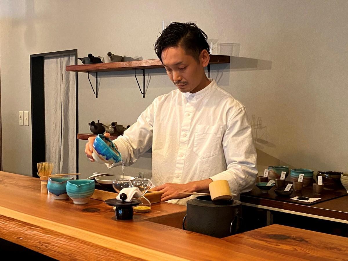 特注したバーカウンターは杉の一枚板。その前でお茶をいれる店主の山本睦希さん
