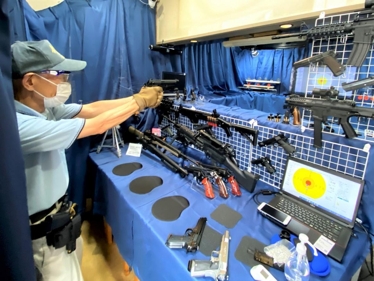 「世界で一番有名な銃のモデル」と説明しながらベレッタM9A1(エムナインエーワン)を構える松井敏明さん