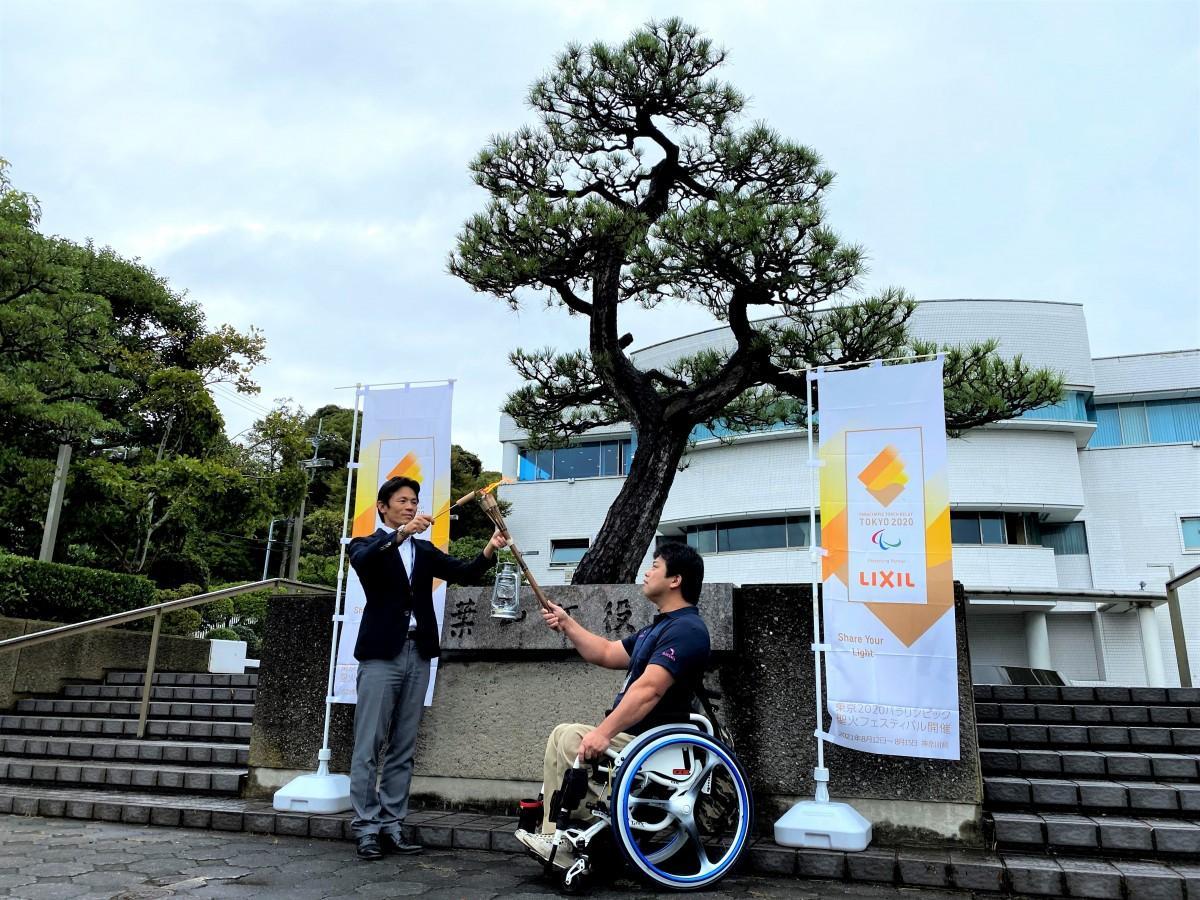 葉山町の役場前で採火式を行う、山梨町長(左)とやり投げ競技選手の小曽根亮選手(右)