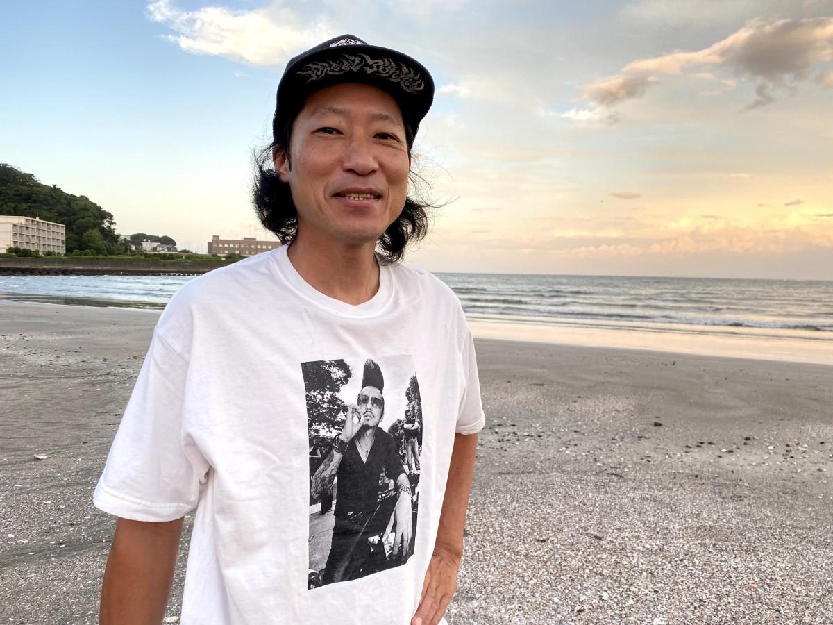 自身の作品「御意見無用」をプリントしたTシャツを着る写真家の元田敬三さん(逗子海岸で)