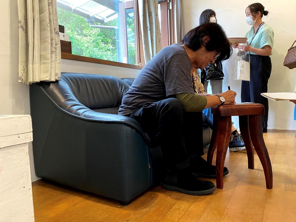 写真集にサインをする森山大道さん。「zushi art gallery」で
